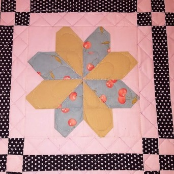 Custom quilting adding highlighting the pieced flower and gridwork sashing